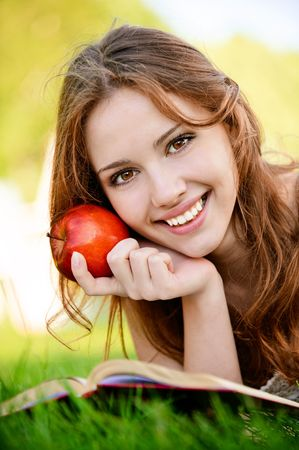 Charming girl with apple lies on green grass and reads book. Stock Photo