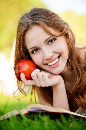 Hotel mit Charme Mädchen mit Apfel liegt auf grüne Gras und liest Buch. Standard-Bild