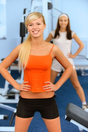 Two beautiful smiling sportswomen do exercises in big sports hall. photo