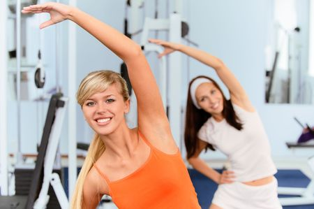 Two beautiful smiling sportswomen do exercises in big sports hall. Stock Photo