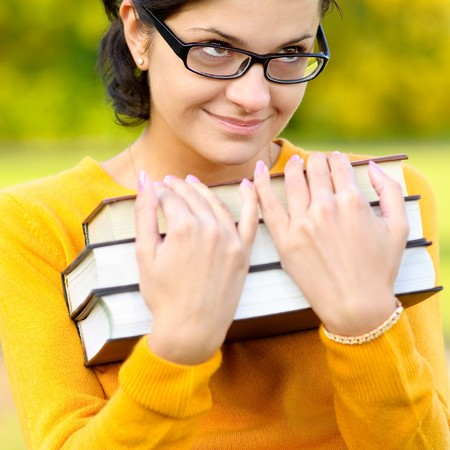 Young woman in yellow sweater holds three books in hands. photo