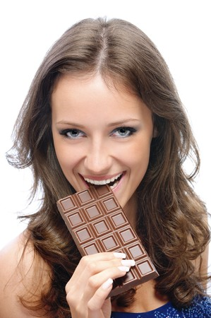 Young beautiful woman bites off slice from chocolate bar, on white background. photo