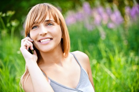 sprightly: Beautiful smiling girl speaks by mobile phone against summer green nature.