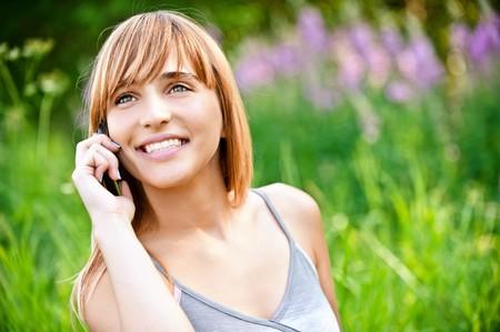 speaks: Beautiful smiling girl speaks by mobile phone against summer green nature.