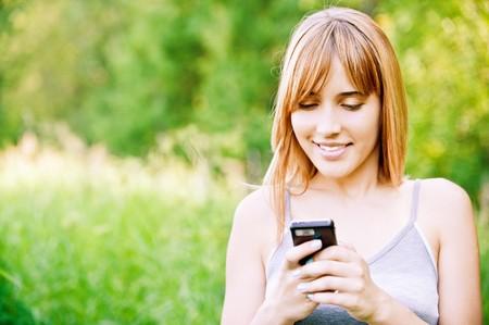 lovely smiling girl reads sms on mobile phone, against green summer garden. Stock Photo - 7435586