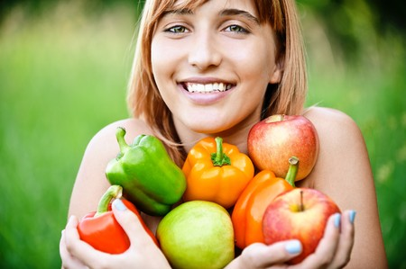 armful: Beautiful laughing girl with apples and sweet pepper, on green summer background. Stock Photo