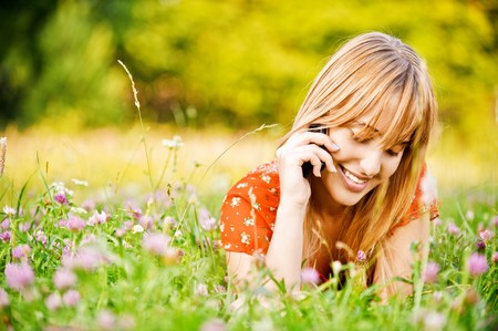talks: Young beautiful smiling woman lies on lawn and talks by mobile phone. Stock Photo