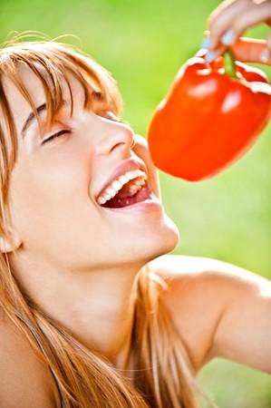 blindly: Joven y bella mujer muerde pimiento dulce rojo, sobre fondo verde.