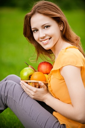 young woman: Portrait of girl with basket apples against green grass.