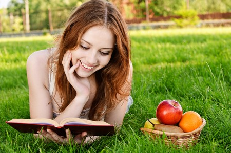 Charming girl with apples lies on green grass and reads book. photo