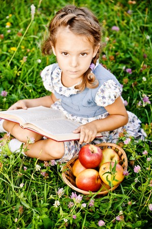 Beautiful little girl with basket of apples reads book, sitting on green lawn. Stock Photo - 7435628