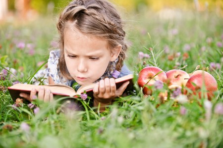 Beautiful little girl with basket of apples reads book, lying on green lawn. photo