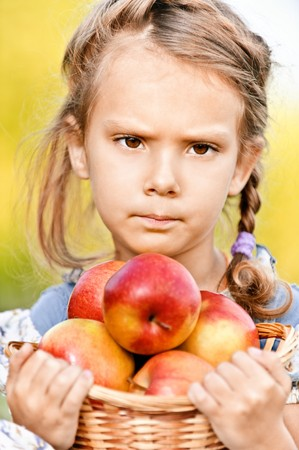 frowned: Small frowned girl holds basket of apples.