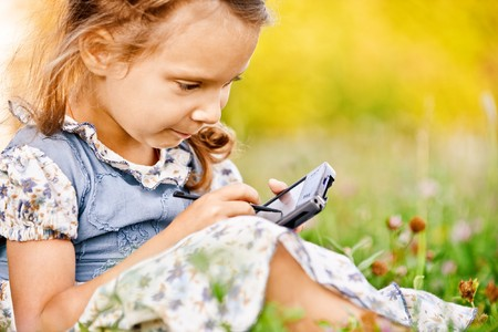 Little girl sits on green grass and draws on PDA. Stock Photo - 7435610