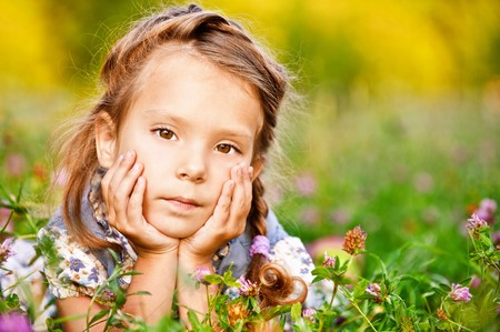 Beautiful little girl lies on green lawn photo