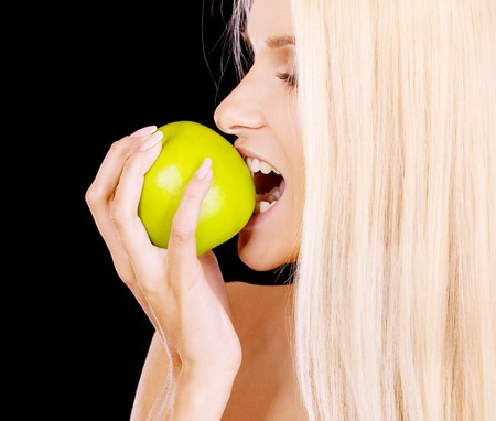 Woman eating green apple, isolated on black background. Stock Photo - 7467918