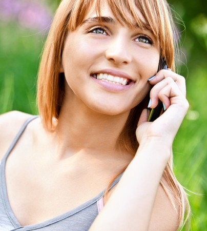 Beautiful smiling girl speaks by mobile phone against summer green nature. photo