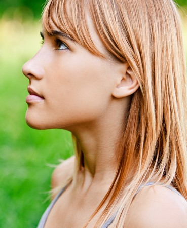 Portrait of girl in profile against green summer nature. photo