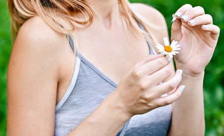 tell fortunes: Girl guesses, tearing off petals on camomile, against green summer garden.