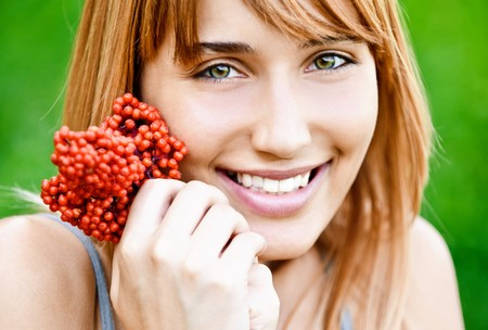 Beautiful smiling girl with red berries in hands against summer green nature. photo