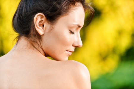 Portrait of young woman with naked shoulders in profile, against autumn nature. photo