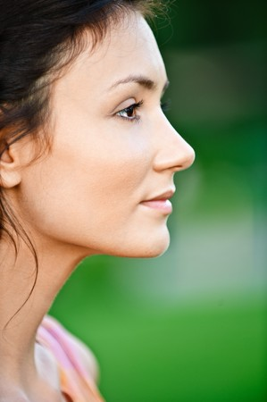 head rest: Portrait of beautiful girl in profile, on green background.