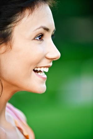 perfil de mujer rostro: Retrato de una hermosa muchacha riendo close up en el perfil, sobre fondo verde.  Foto de archivo
