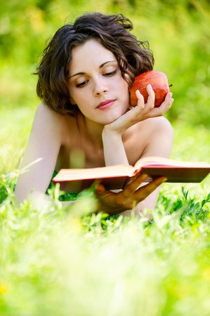 Beautiful young woman reads book, on green summer background. photo