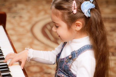 Small dark-haired girl plays piano in educational class. Stock Photo - 7536283