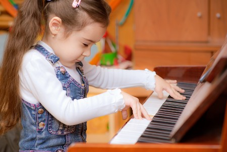 Small dark-haired girl plays piano in educational class. Stock Photo - 7536269