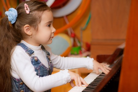 Small dark-haired girl plays piano in educational class. photo
