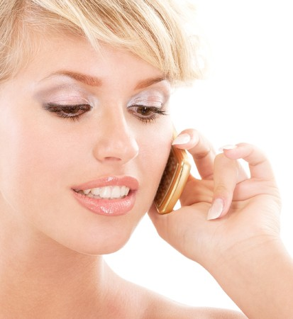 Blond young woman communicates by phone, isolated on white background. photo