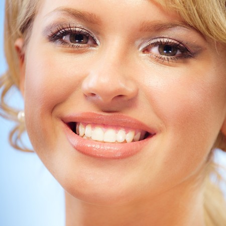 Portrait of charming smiling blonde on dark blue background photo