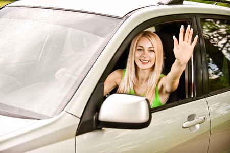 Driver-woman of car waves hand as a sign of greeting. photo