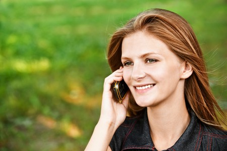 Beautiful smiling girl talks on cellular telephone, against green summer lawn. photo