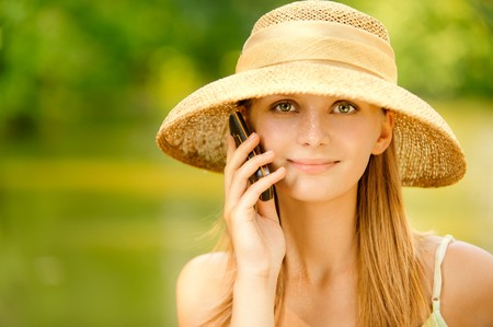 Young beautiful girl in straw hat against lake in city park speaks by mobile phone. Stock Photo - 7536330