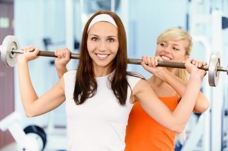 Two beautiful sportwomen make exercise on training apparatus photo