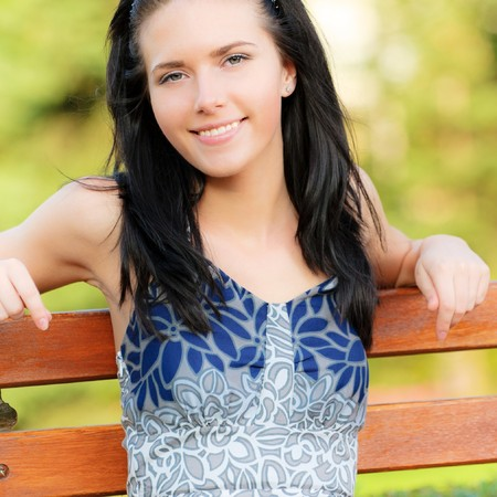 Beautiful dark-haired smiling girl sits on bench in park. photo