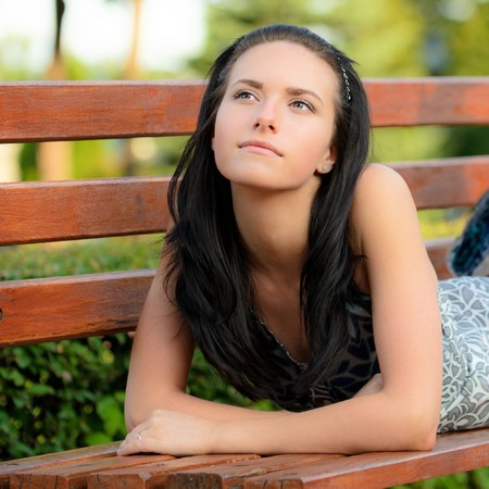 Beautiful dark-haired girl lies on bench in park. photo
