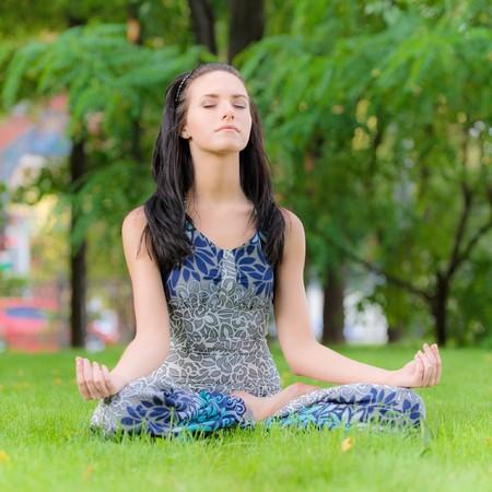 yoga outside: Brunette in pose asana in city park