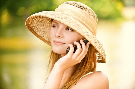 speaks: Young beautiful girl in straw hat against lake in city park speaks by mobile phone. Stock Photo