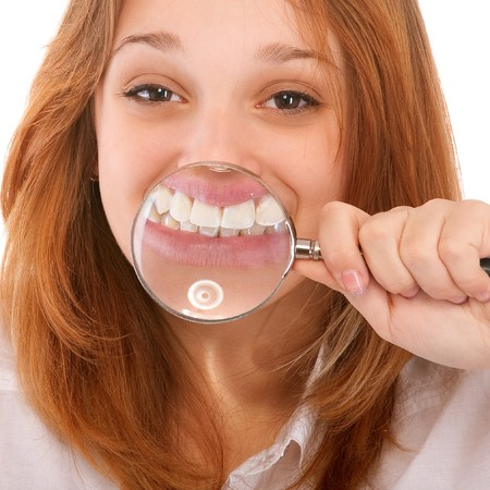 Teeth of young woman through magnifier, isolated on white background. photo