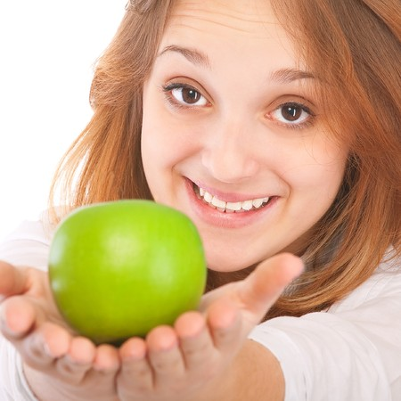 Beautiful young woman holding an apple, isolated on white background. photo