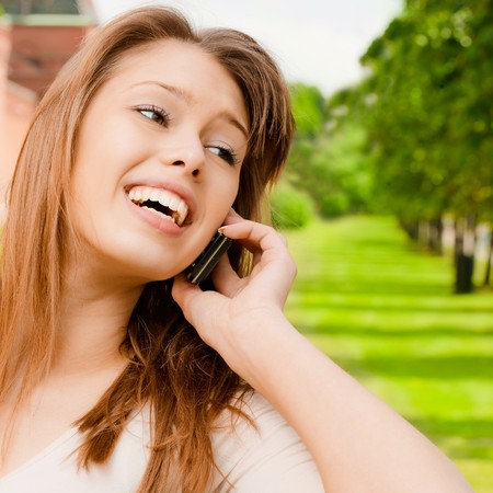 Young laughing woman talks by mobile phone in city park. photo