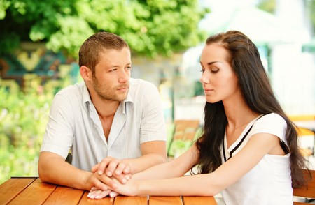 little table: Young couple sit at little table in summer cafe. Stock Photo