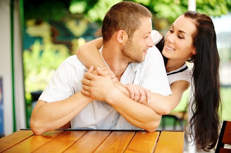 Young couple sit at little table in summer cafe. photo