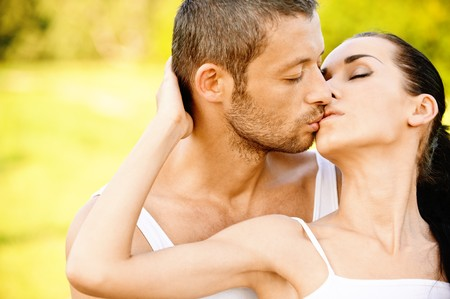 Young beautiful pair kisses against summer garden. Stock Photo - 7692200