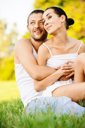 heterosexual couples: Young beautiful couple sits on grass in summer garden. Stock Photo