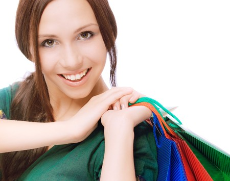 Young beautiful smiling woman with purchases, on white background. photo