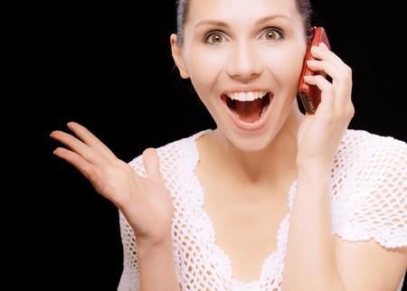 conversa: Entusiasta joven conversaciones por tel�fono m�vil, sobre fondo negro.